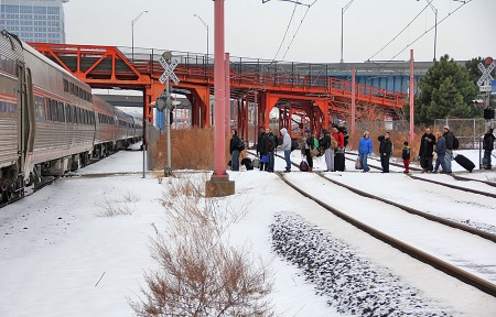 Passengers are lined up waiting to board the train. They are standing on the crossing of the Waterfront Line. The Amtrak station is out of view to the right.
