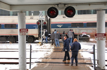 Passengers were allowed to detrain for a smoking stop or to stretch their legs. That break has ended and the last of the passengers is reboarding the train. The view shows the sidewalk that leads from the Amtrak station out across the RTA tracks and toward the platform. The two people in the foreground are the Cleveland Amtrak agents.